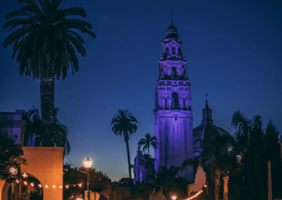 Giant palm tree and the architecture of the Balboa Park museums in the foreground with the colorfully lit California Tower in the background. Photo taken at dusk.